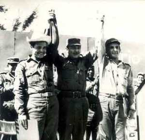 Momento en que Raúl, hace hoy 40 años, tras intercambiar la gorra de sargento de las FAR de Alfredo Luis Fuentes, con el sombrero de yarey de Walter Pupo, miembro de la Columna Juvenil del Centenario, les alza los brazos en gesto simbólico y deja fundado el Ejército Juvenil del Trabajo.